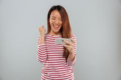 Excited young asian lady play games by phone Royalty Free Stock Photography