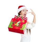 Excited young beautiful girl, wearing red santa claus hat, holding shopping bags Stock Images