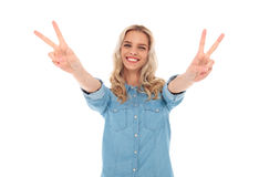 Excited young blonde woman making the victory sign Royalty Free Stock Images