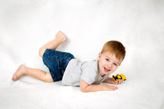 Excited, Young Boy Playing With A Toy Car. A sweet looking little boy plays happily with a toy car. He is laying on his tummy, but kicks his foot up in Royalty Free Stock Photo