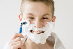 Excited Young Boy Shaving with Plastic Razor Stock Image