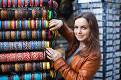 Excited young brunette choosing souvenir for memory. Excited  positive brunette choosing souvenir for memory and smiling Stock Image