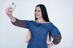Excited young brunette woman making selfie using smart phone. Student girl with long hair in jeans shirt taking photograph with royalty free stock photography