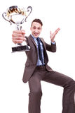 Excited young business man winning a nice trophy. Picture of an excited young business man winning a nice trophy on white background . excited businessman Stock Images