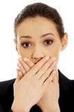 Excited young business woman covering her mouth. Royalty Free Stock Images