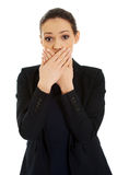 Excited young business woman covering her mouth. Royalty Free Stock Image