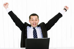 Excited young businessman. Portrait of excited young businessman with hands raised using laptop Stock Photography