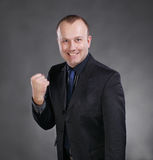 Excited young businessman celebrating victory. On a gray background royalty free stock images