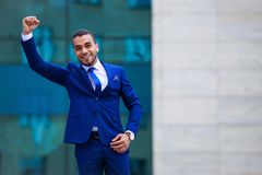 Excited young businessman expressing positivity standing outdoor. S on office building background, copy space royalty free stock photo