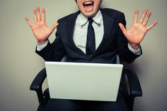 Excited young businessman with laptop. A young businessman is sitting in an office chair and is getting excited about his laptop Stock Photos