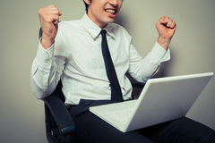 Excited young businessman with laptop. A young businessman is sitting in an office chair and is getting excited about his laptop Stock Images