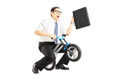 Excited young businessman with leather suitcase riding a small b. Icycle isolated against white background royalty free stock photo