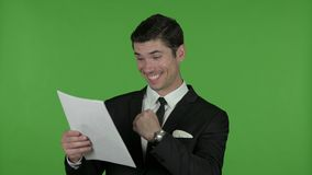 Excited young businessman reading documents, chroma key stock video