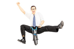 Excited young businessman riding a small bicycle and gesturing h Stock Photos