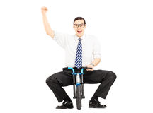 Excited young businessman riding a small bicycle and gesturing h Royalty Free Stock Photography
