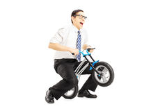 Excited young businessman riding a small bicycle. Isolated on white background Stock Photography