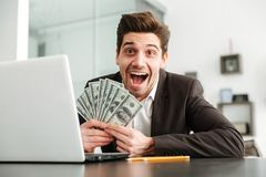 Excited young businessman showing money using laptop computer. Photo of excited young businessman in home indoors. Looking camera showing money using laptop Royalty Free Stock Image