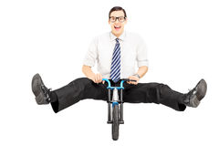 Excited young businessman with tie riding a small bicycle. Isolated on white background Royalty Free Stock Photos