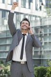 Excited young businessman using cell phone outside office Stock Photos