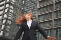 Excited young businesswoman looking up with wind blowing in her hair Stock Images