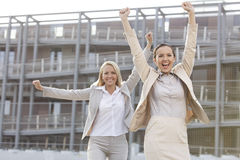 Excited young businesswomen with arms raised against office building Stock Photos