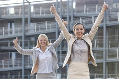Excited young businesswomen gesturing thumbs up against office building stock photo