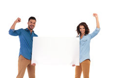 Excited young casual couple holding blank board and celebrate su. Ccess with hands in the air on white background Stock Photo