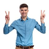 Excited young casual man making the victory sign. On white background Stock Image