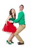 Excited young couple dancing. Interracial weird nerd couple dancing together. Caucasian young men wearing eyeglasses and smiling asian women screaming and royalty free stock images