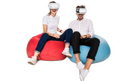 Excited young couple experiencing virtual reality seated on beanbags isolated on white background Stock Image