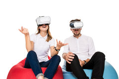 Excited young couple experiencing virtual reality seated on beanbags isolated on white background. A young couple dressed in jeans and white t-shirts Royalty Free Stock Images