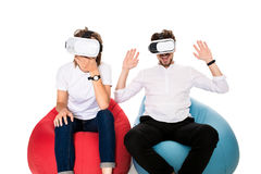 Excited young couple experiencing virtual reality seated on beanbags isolated on white background. A young couple dressed in jeans and white t-shirts Stock Images