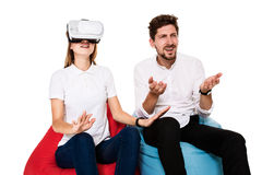 Excited young couple experiencing virtual reality seated on beanbags isolated on white background. A young couple dressed in jeans and white t-shirts Royalty Free Stock Photo
