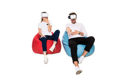 Excited young couple experiencing virtual reality seated on beanbags isolated on white background. A young couple dressed in jeans, white t-shirts and sneakers Royalty Free Stock Photos