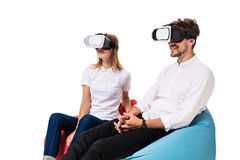 Excited young couple experiencing virtual reality seated on beanbags isolated on white background. A young couple dressed in jeans and white t-shirts Stock Image