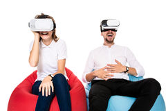 Excited young couple experiencing virtual reality seated on beanbags isolated on white background Stock Photos