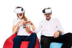 Excited young couple experiencing virtual reality seated on beanbags isolated on white background Stock Images