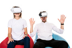 Excited young couple experiencing virtual reality seated on beanbags isolated on white background Royalty Free Stock Photos