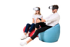 Excited young couple experiencing virtual reality seated on beanbags isolated on white background Stock Photography