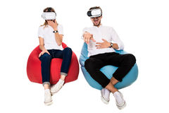 Excited young couple experiencing virtual reality seated on beanbags isolated on white background. A young couple dressed in jeans, white t-shirts and sneakers Stock Photo