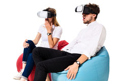 Excited young couple experiencing virtual reality seated on beanbags isolated on white background. A young couple dressed in jeans and white t-shirts, VR Stock Images