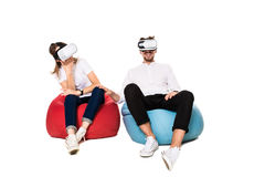 Excited young couple experiencing virtual reality seated on beanbags isolated on white background. A young couple dressed in jeans, white t-shirts and sneakers Stock Image