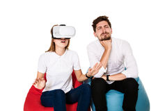 Excited young couple experiencing virtual reality seated on beanbags isolated on white background. A young couple dressed in jeans and white t-shirts, VR Stock Photo