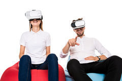 Excited young couple experiencing virtual reality seated on beanbags  on white background. A young couple dressed in jeans and white t-shirts Royalty Free Stock Photos