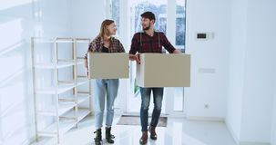 Excited young couple moving to a new spacious house in a sunny day they are smiling holding a big boxes and enjoying the. Moving day stock video
