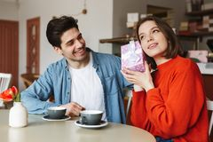 Excited young couple sitting at the cafe table Royalty Free Stock Images