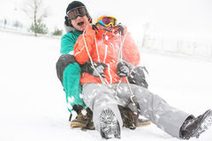 Excited young couple sledding in snow Royalty Free Stock Images