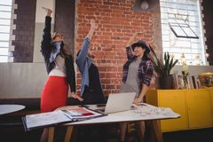 Excited young creative team standing with arms raised. At coffee shop Stock Photo