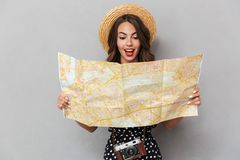 Excited young cute woman wearing hat holding map over grey wall. royalty free stock image