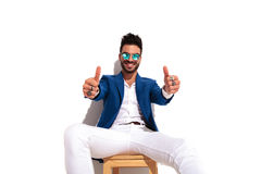 Excited young elegant man sitting and making the ok sign Stock Image